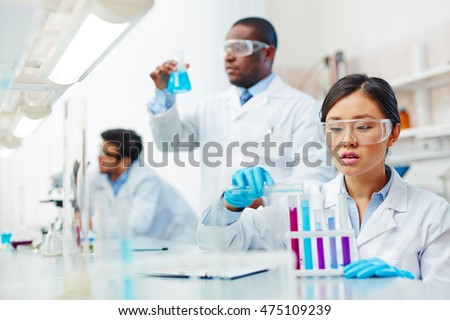 Focused female Asian laboratory scientist in lab coat and safety goggles mixing colored liquid in tubes, male African-American and male Latin-American colleagues working in background.