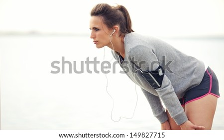 Focused female runner on a break after running workout - stock photo