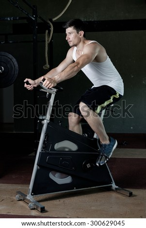 Focused fit man on the spin bike at the gym