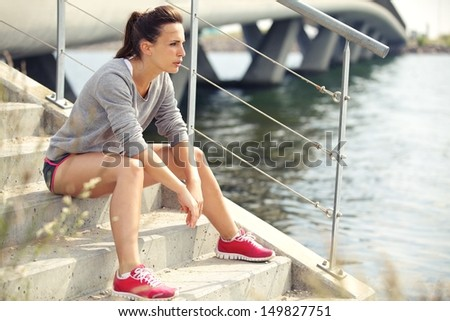 Focused fitness woman resting while preparing for next run - stock photo