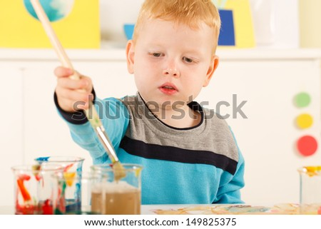 Focused four year old boy painting in art class.