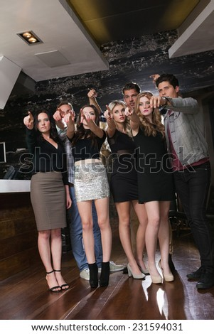 Focused friends standing and pointing away at the nightclub - stock photo