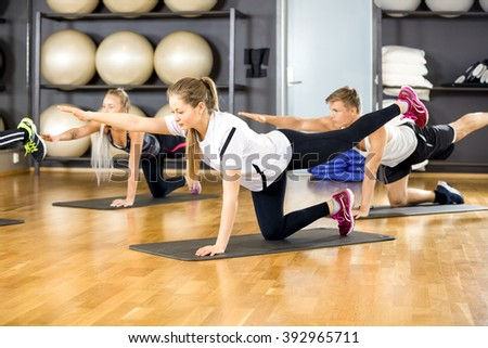 Focused group exercising core strength and balance at fitness gym - stock photo