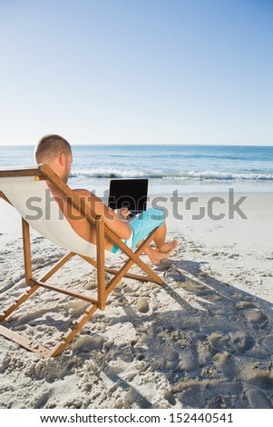 Focused handsome man working on his laptop on the beach