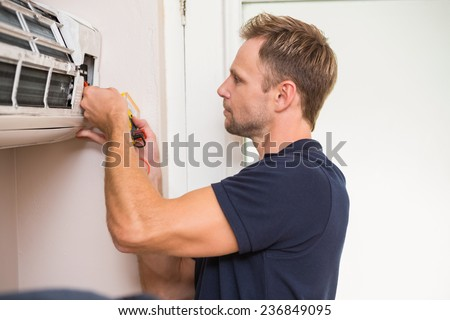 Focused handyman testing air conditioning on the wall - stock photo