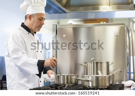 Focused head chef stirring in pot in professional kitchen - stock photo