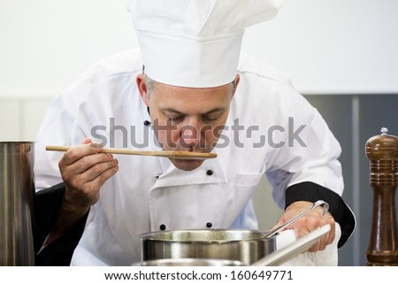Focused head chef tasting sauce with wooden spoon in professional kitchen - stock photo