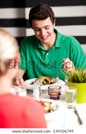 Focused image of a handsome young guy enjoying his meal in a restaurant. - stock photo