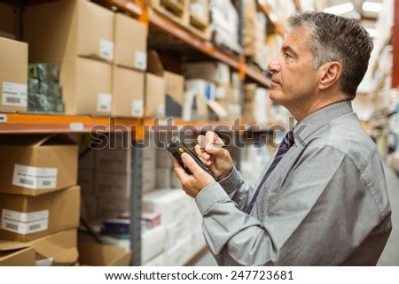Focused male manager using handheld in a large warehouse - stock photo