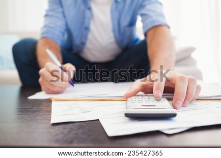 Focused man figuring out his finances in the living room - stock photo