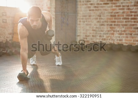 Focused man lifting dumbbell at the gym - stock photo