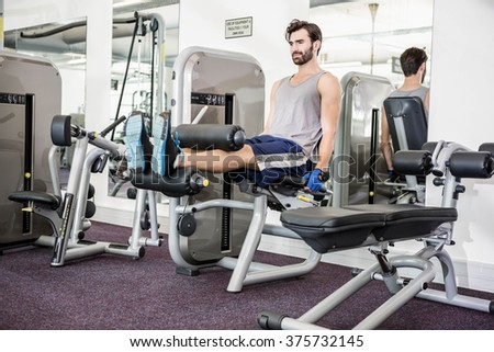 Focused man using weights machine for legs at the gym - stock photo