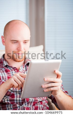Focused man working and playing with tablet computer (lots of co - stock photo