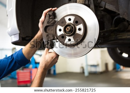 Focused mechanic adjusting the wheel at the repair garage - stock photo