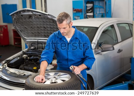 Focused mechanic inflating the tire at the repair garage - stock photo