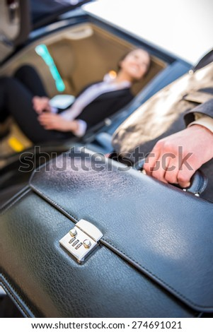 Focused on briefcase image of two  successful confident businesspeople in suits. - stock photo