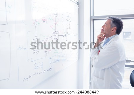 Focused scientist looking equation on whiteboard in laboratory - stock photo