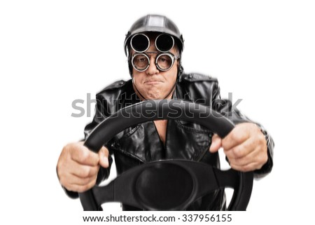Focused senior man with driving helmet and goggles holding a steering wheel and looking at the camera isolated on white background