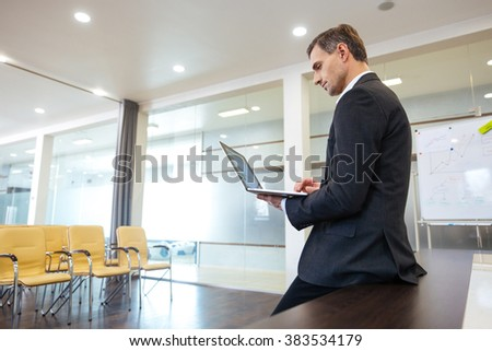 Focused serious businessman preparing for presentation using laptop in empty meeting room - stock photo
