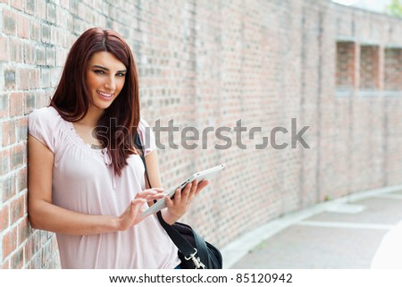 Focused student holding a tablet computer outside a building - stock photo