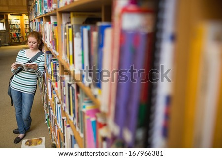 Focused student reading book leaning on shelf in library at the university