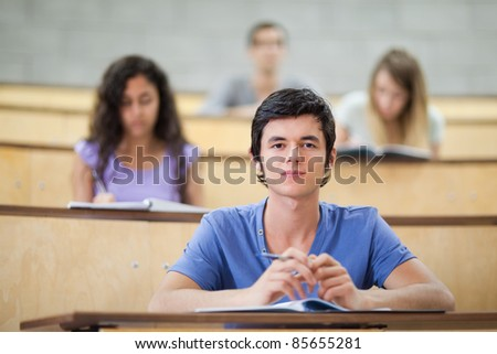 Focused students during a lecture in an amphitheater - stock photo