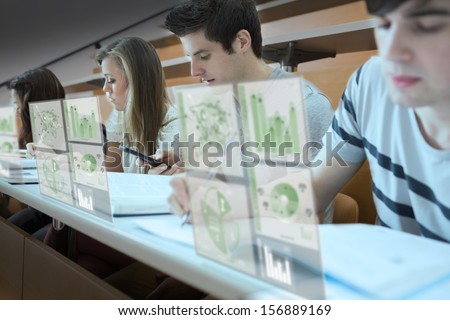 Focused students working on their digital tools in lecture hall - stock photo