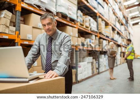 Focused warehouse manager working on laptop in a large warehouse - stock photo