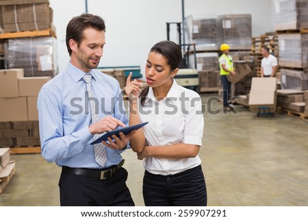 Focused warehouse managers working together in a large warehouse - stock photo