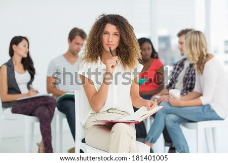 Focused woman looking at camera while colleagues are talking behind her in creative office - stock photo