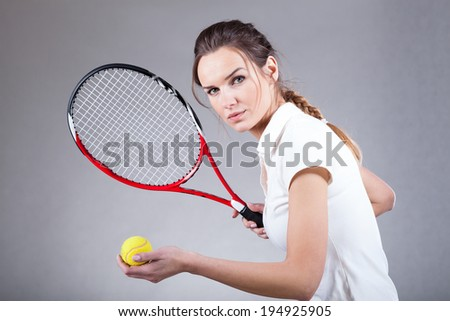 Focused woman playing tennis on isolated background - stock photo