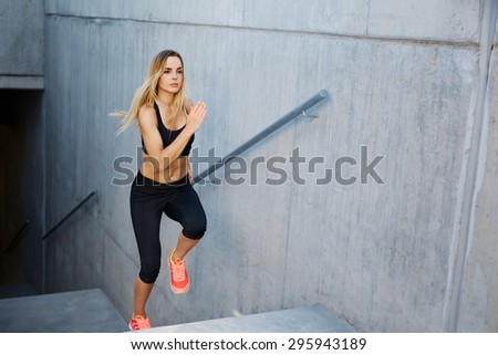 Focused woman running up stairs - stock photo