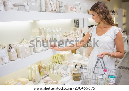 Focused woman with shopping basket browsing products at a beauty salon - stock photo