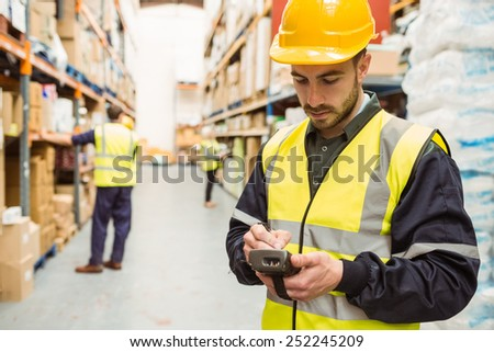 Focused worker wearing yellow vest using handheld in a large warehouse - stock photo