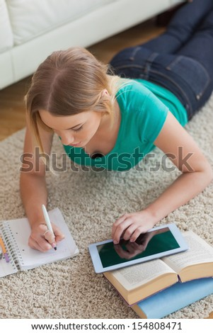 Focused young woman lying on floor using tablet to do her assignment in living room - stock photo