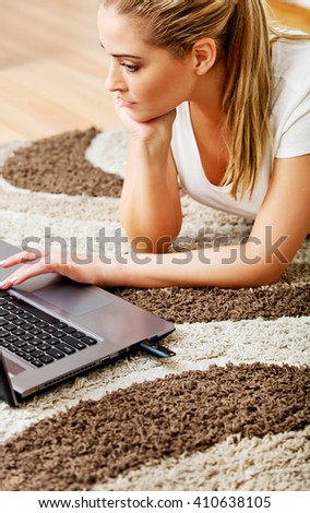 Focused young woman using laptop while lying on floor  - stock photo