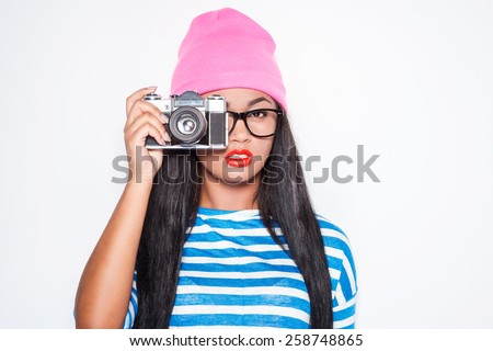Focusing at you. Attractive young African woman in funky clothes focusing at you with her old-fashioned camera while standing against white background  - stock photo