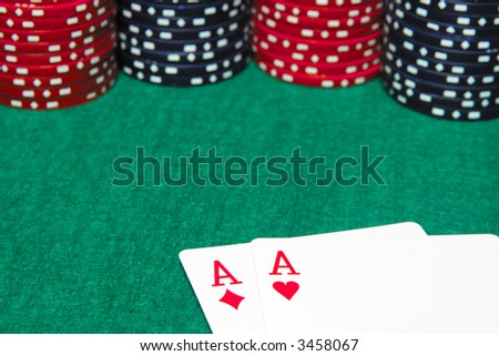 Focusing on a pair of aces and poker chips on a green table.