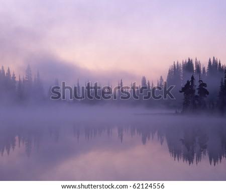 Fog and mist hang over Reflection Lake as dawn breaks; Mount Rainier National Park; Washington State, USA - stock photo