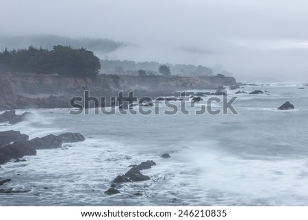 Fog and Pacific ocean waves wash against the rocky shore of California. Wave energy has helped shape the shoreline of the entire west coast.