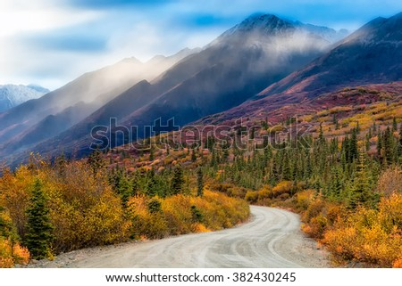 Fog and rain clouds decorate the peaks of the Clearwater Mountains along the Denali Highway in Alaska - stock photo