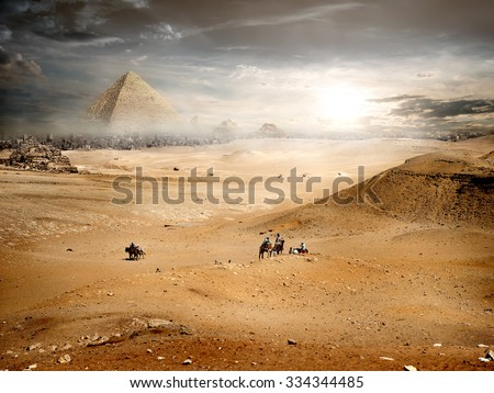 Fog and storm clouds over pyramid in desert - stock photo