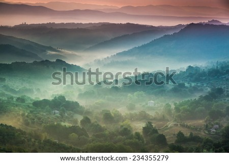 Fog at dawn over the valley in Tuscany - stock photo