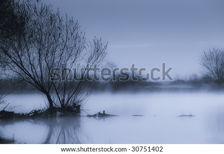 Fog at waterside in early morning. Foggy scene. - stock photo