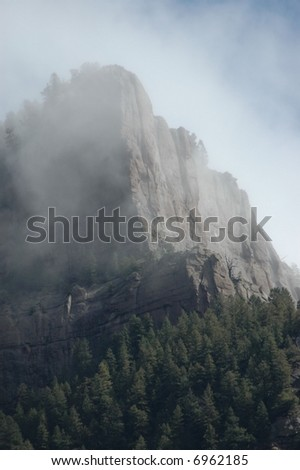 Fog & Clouds on Rock Cliff in Colorado - stock photo