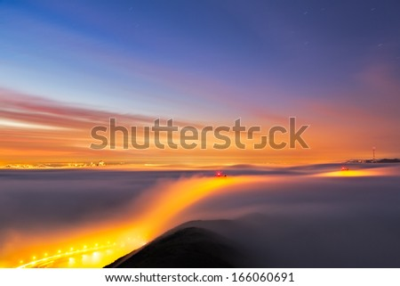 Fog flows into the San Francisco Bay and over the famous Golden Gate bridge as the sunrise lights up the clouds in the sky.