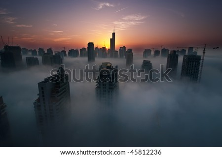 Fog in Dubai Marina at dawn - stock photo