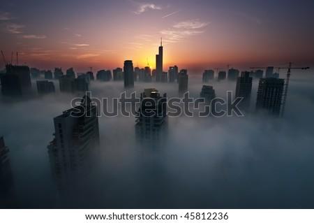 Fog in Dubai Marina at dawn - stock photo
