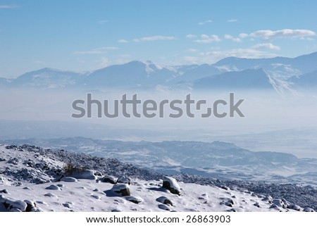 Fog in mountain valley in a sunny winter day - stock photo
