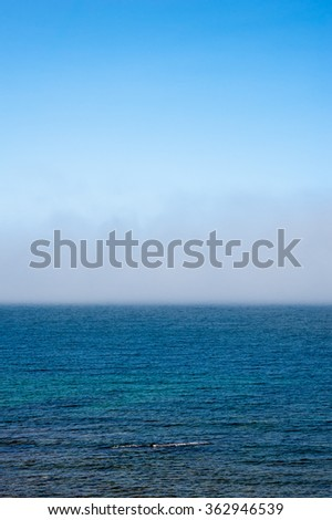 Fog low over shallow wavy water under blue sky.